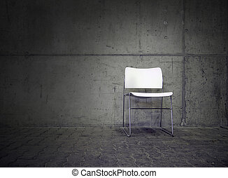 white chair in spotlight with concrete wall in the...