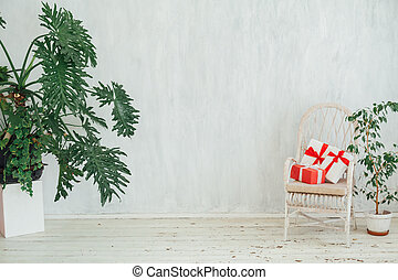 white chair with gifts with home plants in the interior of a vintage gray room