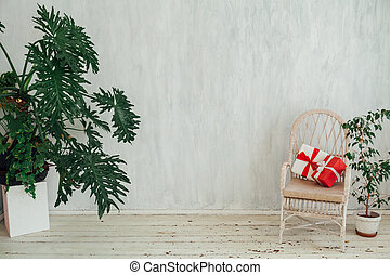 white chair with plants and gifts in the gray room