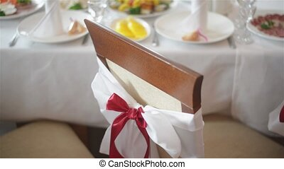 White chair with red bow close up indoors at wedding banquet or reception. Wedding decorations. The Big Day.