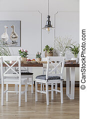 White chairs at wooden table in cottage dining room interior with flowers and poster. Real photo
