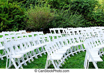 White chairs in the park. - Empty white chairs before...