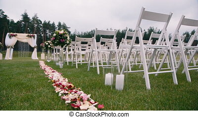 White chairs on the green grass. A place for wedding ceremony