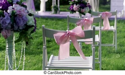 White chairs with pink bows close up outdoors at wedding verinke. Wedding decorations.