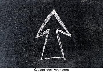 White chalk drawing in arrow shape on black board background