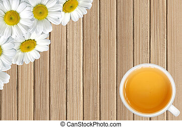 white chamomile flowers and tea cup on wooden table background
