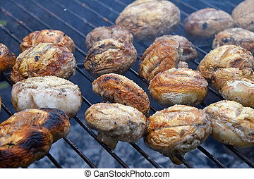 White champignons mushrooms on grill