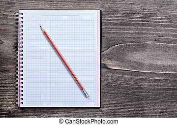 White checked copybook with pencil on pine brown wooden board ed