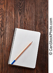 White checked copybook with pencil on pine brown wooden board