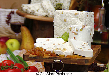 white cheese with raisins and grapes on a knife board, on a background with fruit and vegetables in a lush setting of fruit and vegetables and onther cheeses