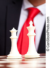 White chess king and queen in front of business suit