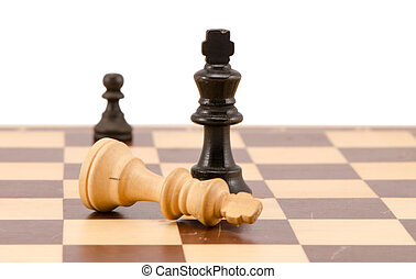 white chess king lie near winner black legs