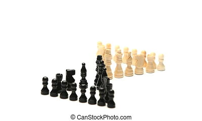 White chess pieces facing black chess pieces rotating on a...