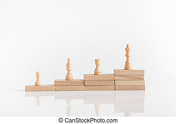 White chess pieces on a stepped stack of wooden blocks with queen piece