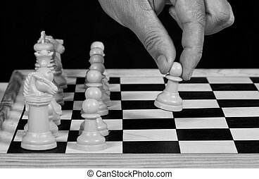 White chess pieces with hand playing