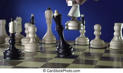 White chess player knocks down the black king with his piece