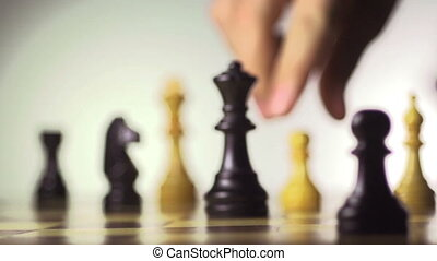 White chess player knocks down the black king with his...