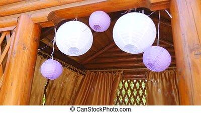 white Chinese lanterns hanging under wooden rack. - white...
