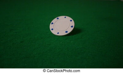 White chip spinning and red dice falling on casino table in...