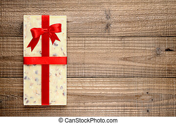 White chocolate with ribbon on wooden background