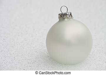 white christmas bauble on the frozen ground