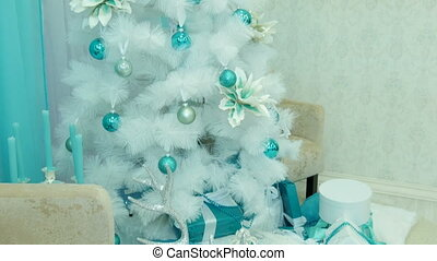 White Christmas tree decorated with gifts.