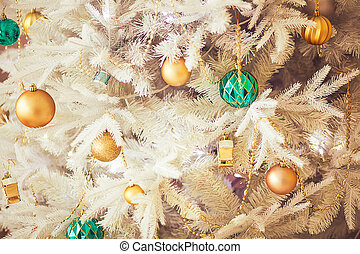 White Christmas tree with gold and green baubbles, close up