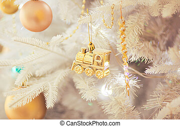 White Christmas tree with gold christmas ornament, close up