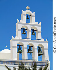 White church bell tower against blue sky in Greece