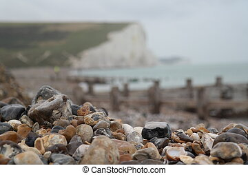 Focus on marbles with the background of white cliffs in Seven sister country park
