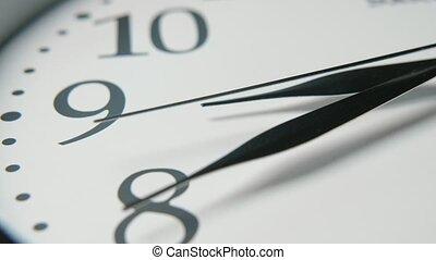White clock face with three sharp black hands showing twenty...
