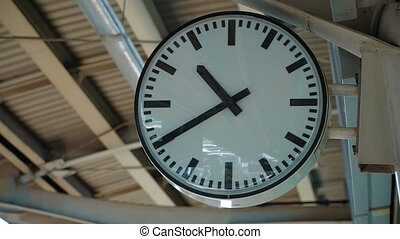White clock ticking at the train station.