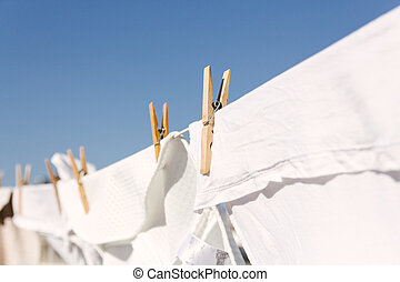 White clothes hung out to dry in the bright warm sun - White...