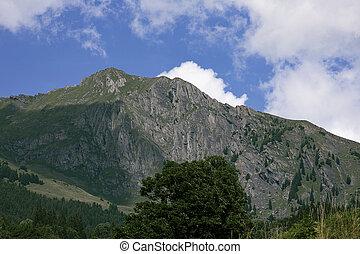 White cloud on blue sky behind the mountain peak. Summer in alps. Switzerland.