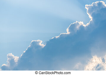 White clouds and blue sky with ray of sun coming through