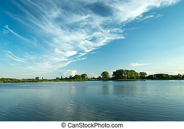 White clouds blowing in the blue sky over a peaceful lake