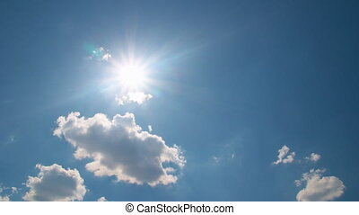 White clouds flying on blue sky with sun rays - Time-lapse...
