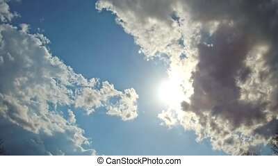 White clouds flying on blue sky with sun rays motion background
