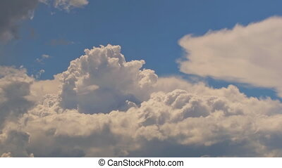 White clouds flying on blue sky with sun rays - White puffy...
