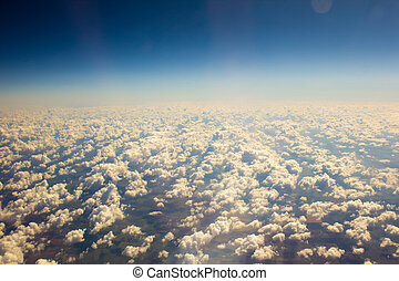 White clouds in blue sky. Aerial view from airplane.
