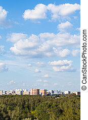 white clouds in blue sky over city and green woods