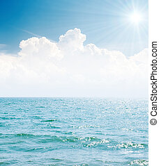 white clouds in blue sky with sun and sea
