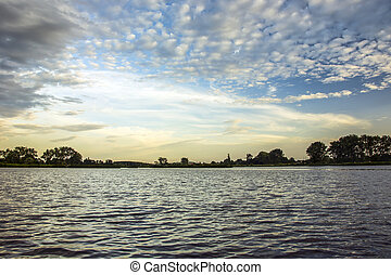 White clouds in the sky over a calm lake