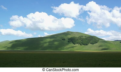 White clouds moving over mountains, Castelluccio of Norcia. Sunny day in Umbria, Apennine Mountains.