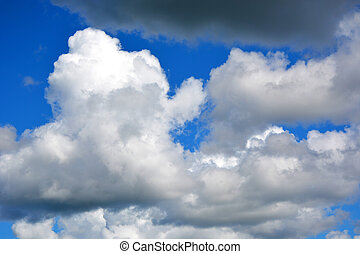 White clouds on a blue sky at noon. Beautiful atmospheric phenomenon. Natural horizontal background.