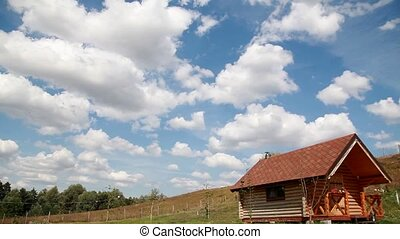 white clouds on the blue sky over the wooden house