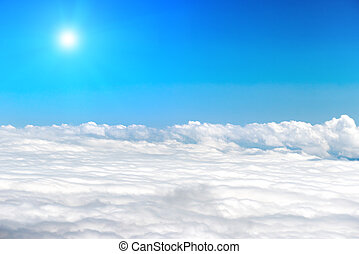White clouds on the blue sky with shining sun