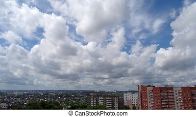 White clouds running over city, bright blue sky. Timelaps. -...