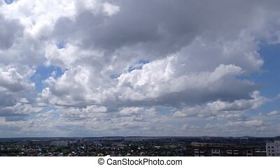 White clouds running over city, summer day-time. Timelaps. -...