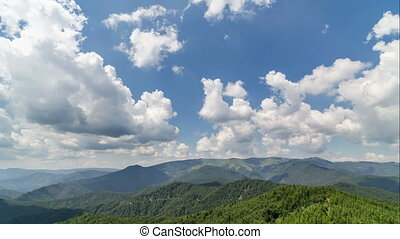 White clouds towering over blue sky and green forest landscape time lapse